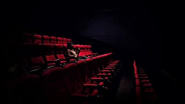 A woman sits alone in a darkened cinema.