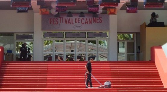 Man vacuums red carpet on stairs at Cannes cinema